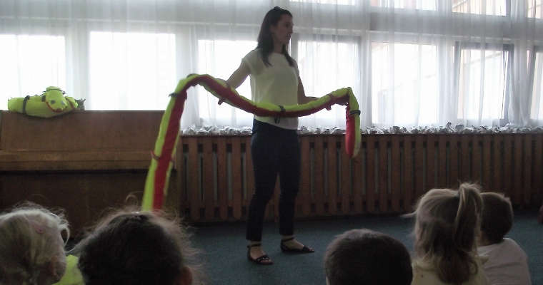 Pracownik WORD Warszawa prezentujący grupie przedszkolaków jeden z odblaskowych gadgetów, odblaskowy wąż, rozdawanych przedszkolakom podczas spotkania poświęconego bezpieczeństwu na drodze