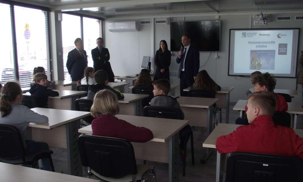 Zdjęcie sali wykładowej Miasteczka Ruchu Drogowego. Na sali grupa młodzieży uczestniczącej w wykładzie o bezpieczeństwie na drodze.